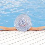 Woman laying in pool with sunhat on